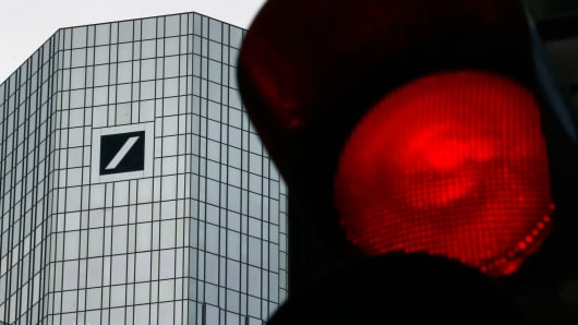 A red traffic light is seen next to the headquarters of Germany's Deutsche Bank in Frankfurt, Germany, January 26, 2016.