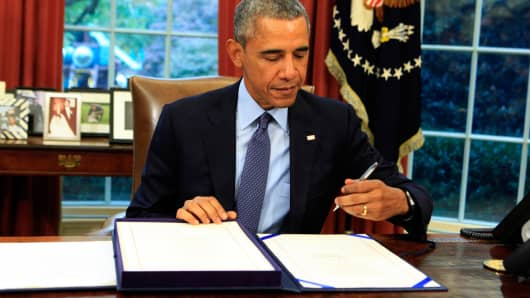President Barack Obama signs the bipartisan budget bill in the Oval Office of the White House, November 2, 2015.