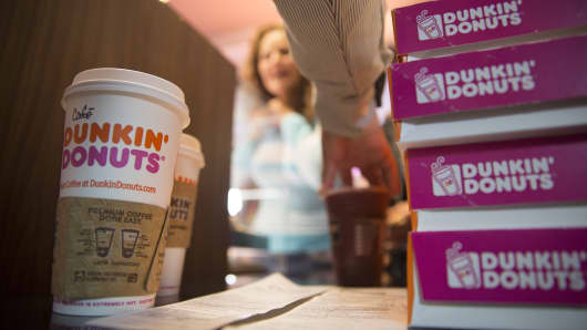 Dunkin brands new ceo modernizes iconic coffee company a dunkin donuts worker hands cups of coffee and boxes of donuts to a customer malvernweather Gallery
