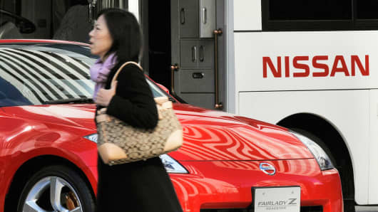A pedestrian passes before a vehicle from auto giant Nissan Motors at the company's showroom.