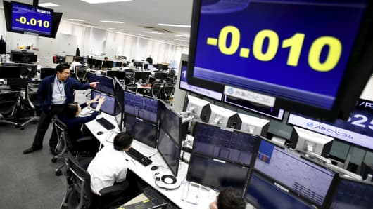 Employees of a foreign exchange trading company work under monitors displaying the 10-year Japanese government bond yield in Tokyo, Feb. 9, 2016.