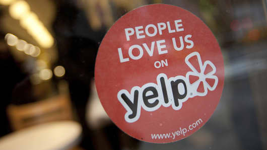 The Yelp logo is displayed in the window of a restaurant in New York.