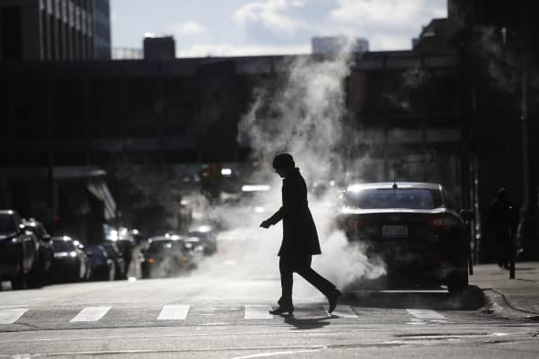 A woman walks through steam rising from the ground along Fort Street in Detroit, Michigan.