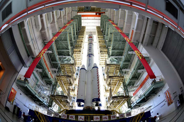 The Shenzhou 9 manned spacecraft, Long March 2F rocket and escape tower wait to be transferred to the launchpad at the Jiuquan Satellite Launch Center, Gansu province June 9, 2012.