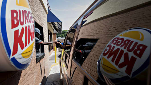 An employee assists a customer at the drive-through of a Burger King restaurant in Peoria, Illinois.