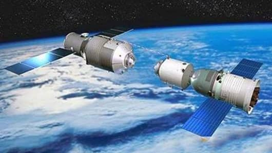 In this TV grab, Chinas latest manned space capsule docked with the lab, the Tiangong-1 in space, 13 June 2013.
