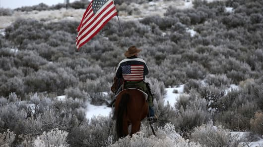 Anti-government militant carries an American flag as he rides his horse on the Malheur National Wildlife Refuge.