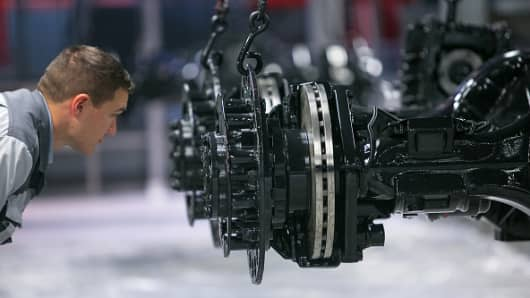 n employee inspects a truck axle hanging on the assembly line inside the MAN SE factory in Germany.