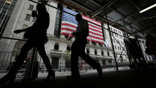 Pedestrians pass in front of the New York Stock Exchange.
