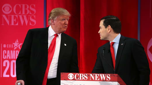 Republican presidential candidates Sen. Marco Rubio (right) listens to Donald Trump (left) during a break of a CBS News GOP Debate in Greenville, South Carolina.