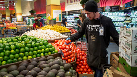 A Whole Foods employee stocks produce in Oakland, Calif.