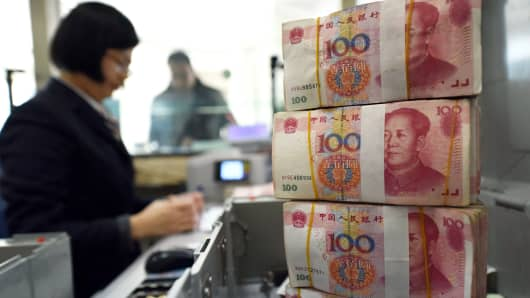 An employee counts 100-yuan banknotes at a bank in Lianyungang, China.
