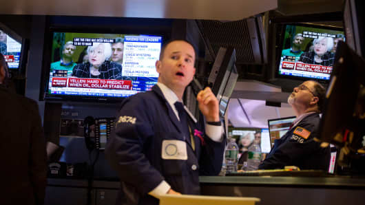 Traders work on the floor of the New York Stock Exchange (NYSE) as Janet Yellen, chair of the U.S. Federal Reserve, is seen speaking on a television screen in New York.