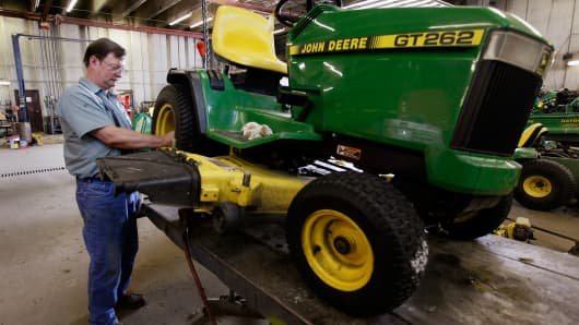 A man works on a customer's John Deere lawn tractor at the Buck Bros. dealership in Hampshire, Illinois.