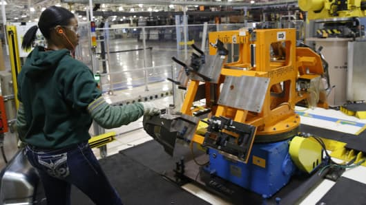 Auto worker Imani Long assembles parts that will be welded by a robot for the Dodge Dart rear wheel house at Fiat Chrysler Automobiles NV's Warren Stamping Plant in Warren, Michigan.