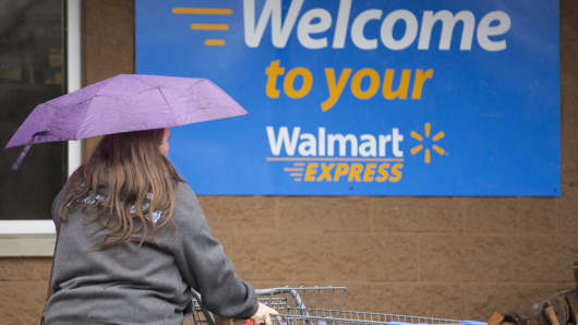 A woman carries umbrella while walking toward a Wal-Mart Express store in Richfield, N.C.