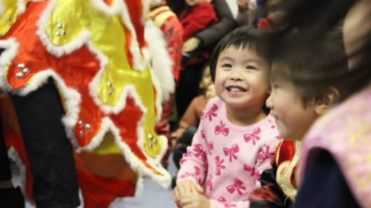 A preschooler smiles during a Chinese New Year celebration at her school the Little Star of Broome Street Early Childhood Center.