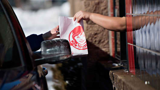 An employee hands a customer their order at the drive-thru window of a Wendy's restaurant in Peoria, Illinois.