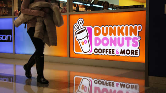 A pedestrian passes a Dunkin' Donuts location at the Dallas/Fort Worth International Airport.