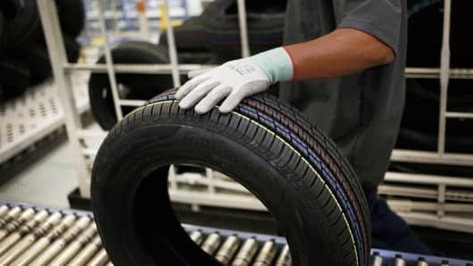 A worker moves an automotive tire down a conveyor belt at the Continental Tire Sumter plant distribution warehouse in Sumter, South Carolina.