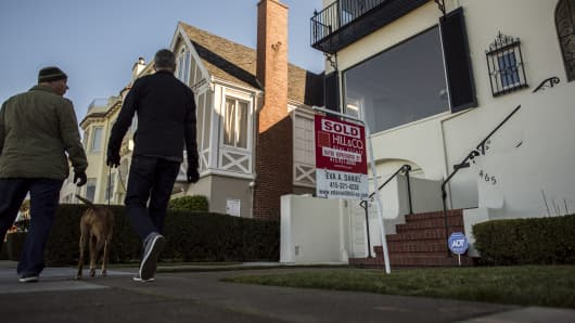 "Pedestrians walk past a home with a ""Sold"" sign in San Francisco."