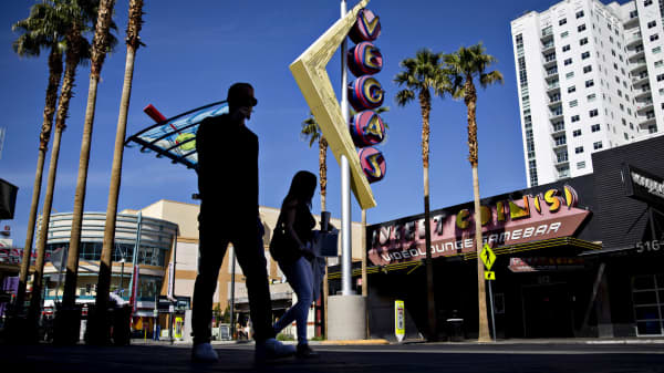 Pedestrians walk past a Vegas sign on Fremont Street in Las Vegas, Nevada.