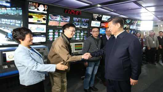 Chinese President Xi Jinping (R, front) shakes hands with staff members at the control room of China Central Television in Beijing, capital of China, on Feb. 19, 2016