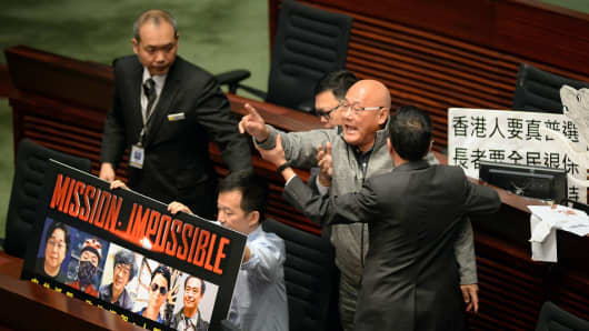 Albert Chan (Center) is removed from the Legislative Council Chambers for interjecting during Chief Executive Leung Chun-ying 2016 Policy Address in the Admiralty district of Hong Kong on January 13, 2016.