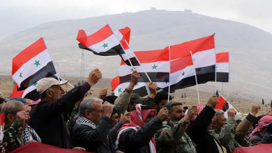 Syrian volunteers and their relatives wave the national flag and portraits of President Bashar al-Assad as they celebrate at the end of a paramilitary training conducted by the Syrian army in al-Qtaifeh.