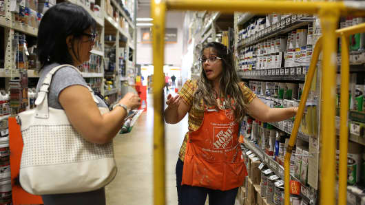 Home Depot employee helps a customer as she shops in the paint department at the store in Miami.
