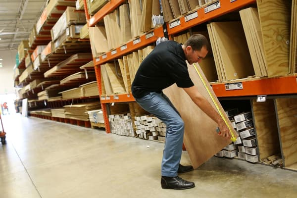A customer measures a piece of plywood at a Home Depot in Miami, Florida.