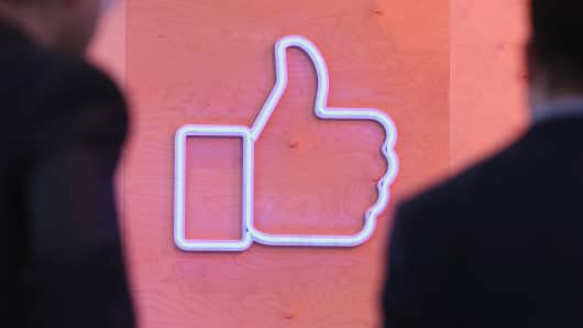 People walk past the Facebook 'Like' symbol at the Facebook Innovation Hub on February 24, 2016 in Berlin, Germany.