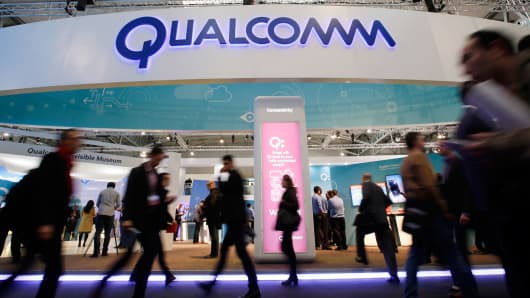 People walk past Qualcomm's stand during the Mobile World Congress in Barcelona, Spain February 24, 2016.