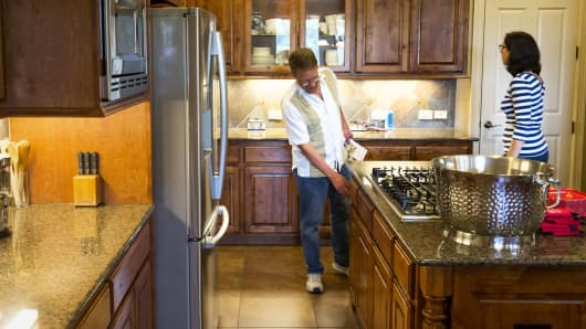 Prospective home buyers view a kitchen while touring a house for sale in Helotes, Texas.