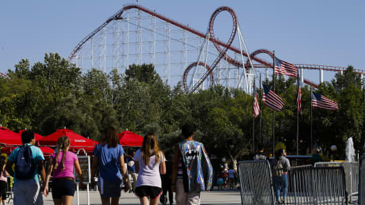 Visitors walk towards a roller coaster at Six Flags Magic Mountain in Valencia, California.