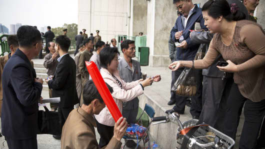 People buy inflatable clappers before a football match at the Kim Il Sung Stadium in Pyongyang October 8, 2015.