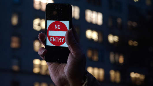 A protestor holds up an iPhone that reads, 'No Entry' outside of the the Apple store on 5th Avenue on February 23, 2016 in New York City.