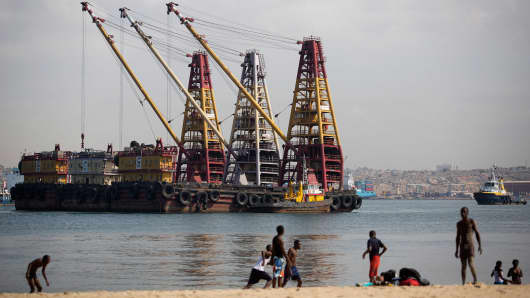 Local youths play on the beach beyond heavy lifting shipping cranes on barges moored off the shoreline in Luanda, Angola.