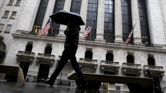 A pedestrian with an umbrella passes outside the New York Stock Exchange.