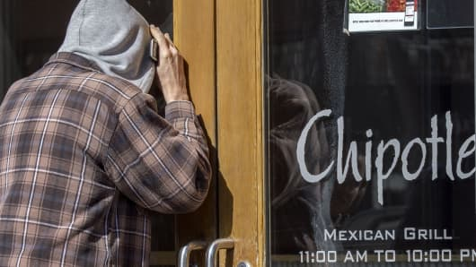 A man looking to eat lunch, looks thru the locked front door of the Chipolte Restaurant February 8, 2016, in the Washington, DC, commmunity of Georgetown.