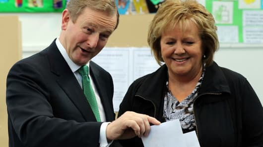 Irish Prime Minister and Fine Gael leader Enda Kenny (L) and his wife Fionnuala vote at St Anthony's Primary School in Castlebar, western Ireland, on February 26, 2016, during a general election.