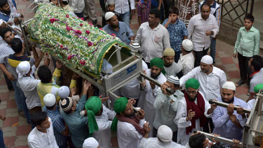 Indian mourners carry coffins with the bodies of some of the 14 family members murdered at home, during their funeral in Mumbai on February 28, 2016.