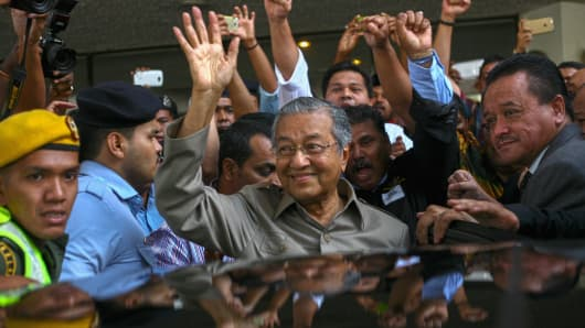 Former Malaysia Prime Minister Mahathir Mohamad waves to media as he leaves the '1Malaysia Development Berhad' (1MDB) forum after inspector-general of Police Khalid Abu Bakar advised the forum should be cancelled due to security concerns, at t