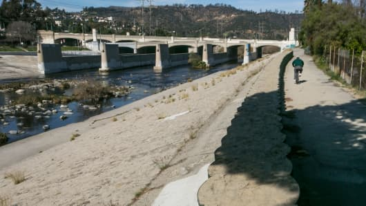 A cyclist rides along recently installed temporary flood control walls along the L.A. River in Los Angeles Feb. 12, 2016. The US Army Corps of Engineers installed about three miles of temporary barriers along the river through Griffith Park, Atwater Village, and Silver Lake, to increase the amount of water the river can hold during El Nino season. Where did El Nino go?