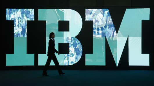A woman walks past the IBM logo