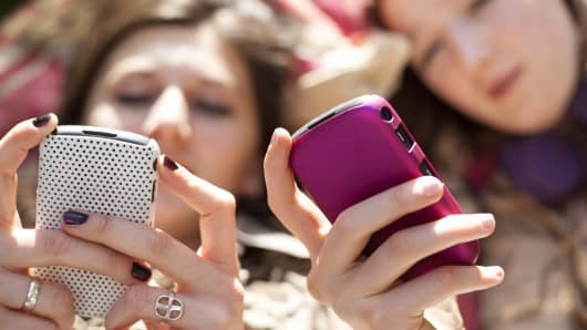 Teenage girls using cell phones