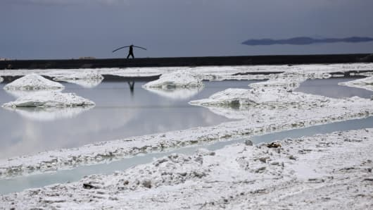 A worker walks near an evaporation pool where lithium bicarbonate is isolated from salt brine during the process of lithium production at the Uyuni Salt Flats in Uyuni, Bolivia.