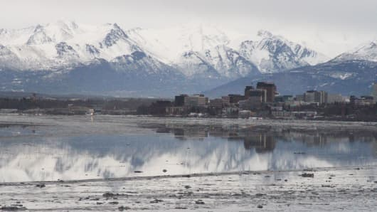 The Chugach Mountains and the building of downtown Anchorage, Alaska, are reflected in the still waters of Cook Inlet.