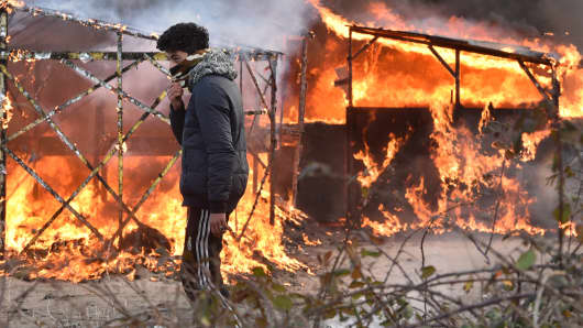 A migrant walks past shacks burning during the dismantling of half of the 'Jungle' migrant camp in the French northern port city of Calais, on February 29, 2016. Clashes broke out between French riot police and migrants on February 29 as bulldozers moved into the grim shantytown on the edge of Calais known as the 'Jungle' to start destroying hundreds of makeshift shelters.