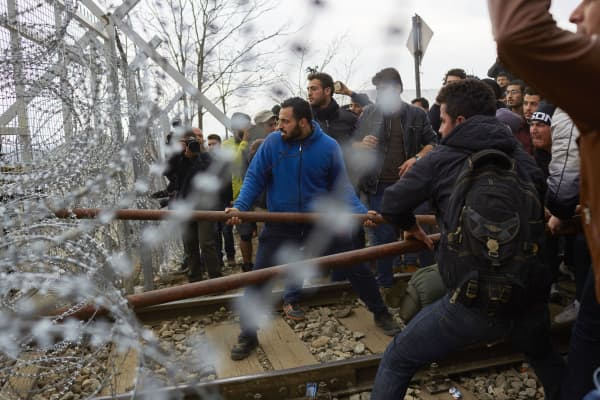 Refugees break the fence on the Greek-Macedonia border on February 29, 2016 in Idomeni, Greece. A group of refugees forced the gate in an attempt to enter Macedonia.